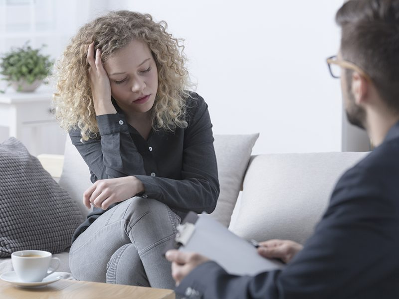 Young worried woman touching her head during psychotherapy